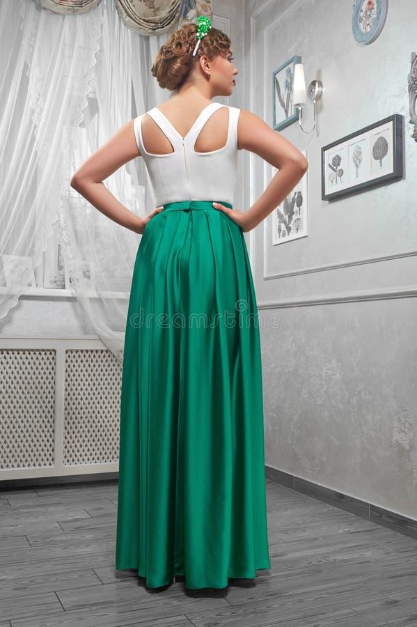 Giovane donna, bello castana in un vestito da verde lungo, mani sopra fotografia stock