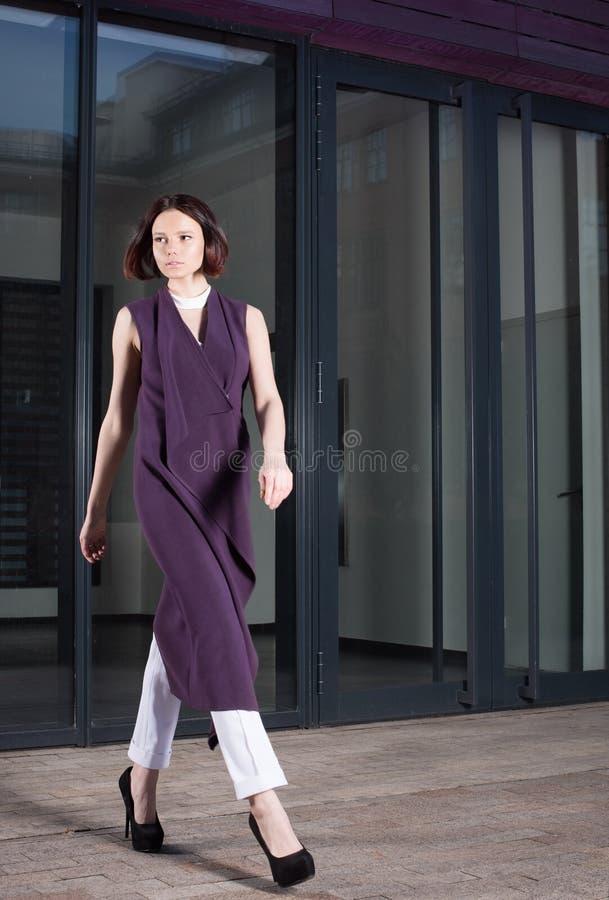 Giovane donna in bello vestito porpora che cammina giù la via immagini stock