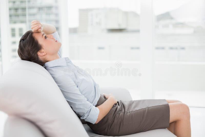Giovane donna ben vestito stanca che si siede sul sofà fotografia stock