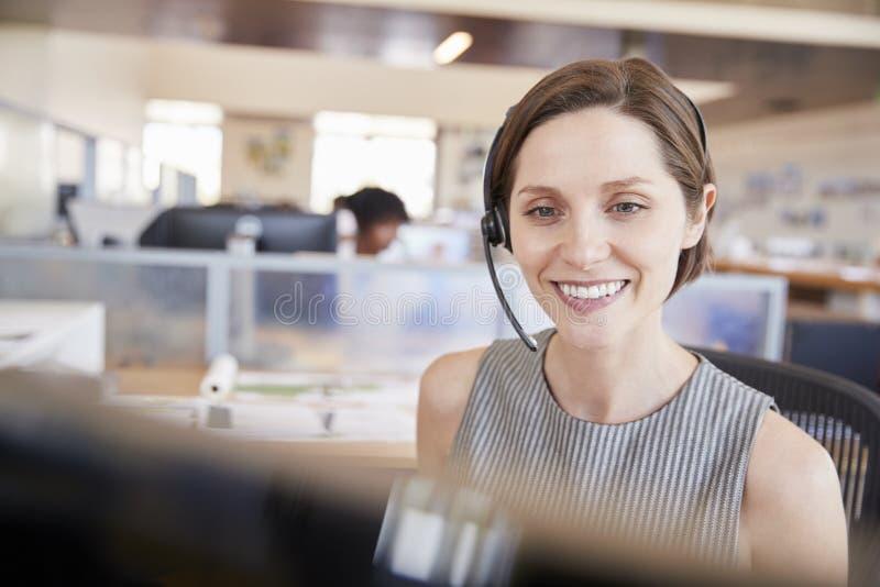 Giovane donna bianca che lavora in un call-center fotografie stock