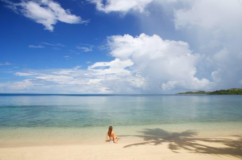 Giovane donna in bikini che si siede su una spiaggia tropicale, Nananu-io-Ra i immagini stock libere da diritti