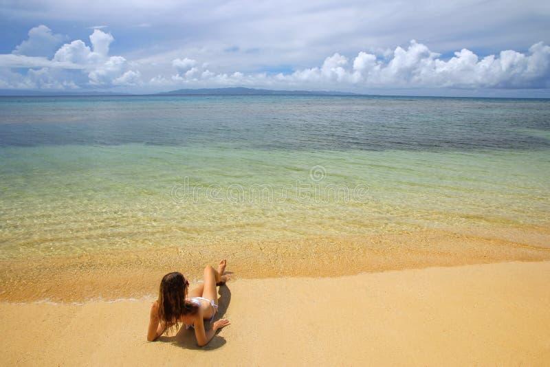 Giovane donna in bikini che si trova sulla spiaggia sull'isola di Taveuni, Figi fotografia stock