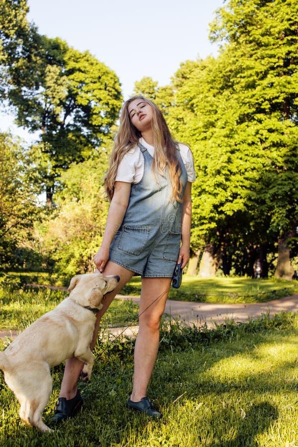 Giovane donna bionda attraente che gioca con il suo cane in parco verde all'estate, concetto della gente di stile di vita fotografie stock