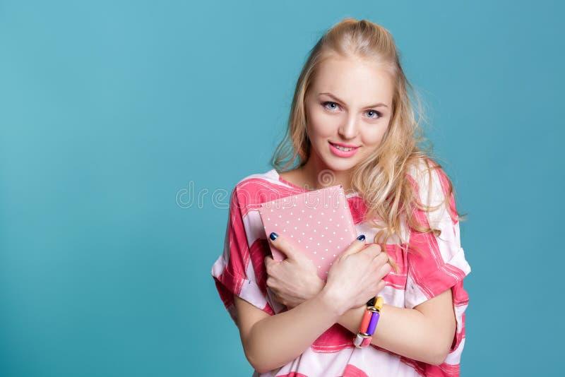 Giovane donna bionda attraente che tiene libro rosa su fondo blu fotografia stock libera da diritti