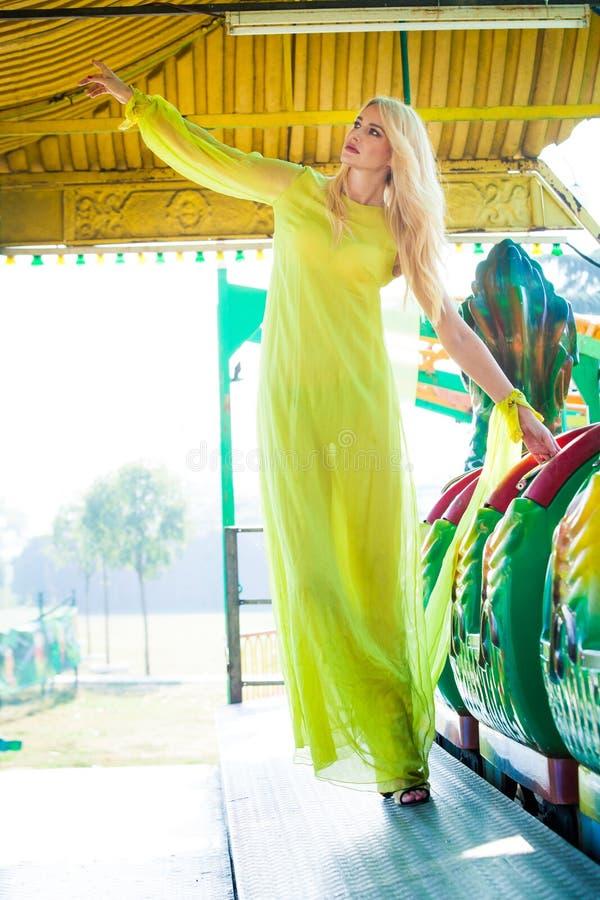 Giovane donna bionda attraente di modo in vestito giallo elegante lungo di estate del parco di divertimenti immagine stock libera da diritti