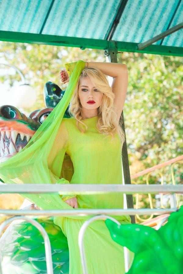 Giovane donna bionda attraente di modo in vestito giallo elegante lungo di estate del parco di divertimenti immagini stock libere da diritti