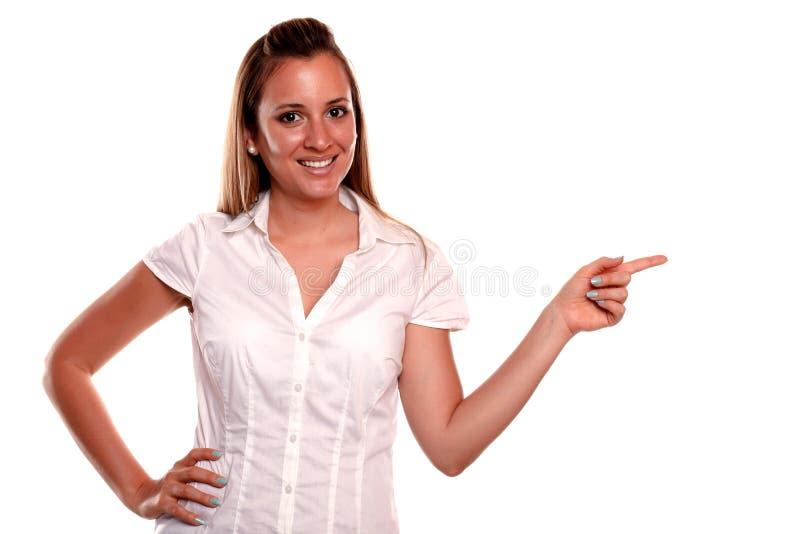 Giovane donna bionda Charming che indica la sua parte di sinistra fotografie stock