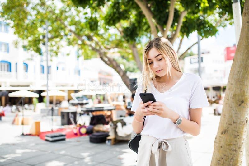 Giovane donna bionda che cammina e che scrive sul telefono nella via in un giorno di estate soleggiato fotografia stock libera da diritti
