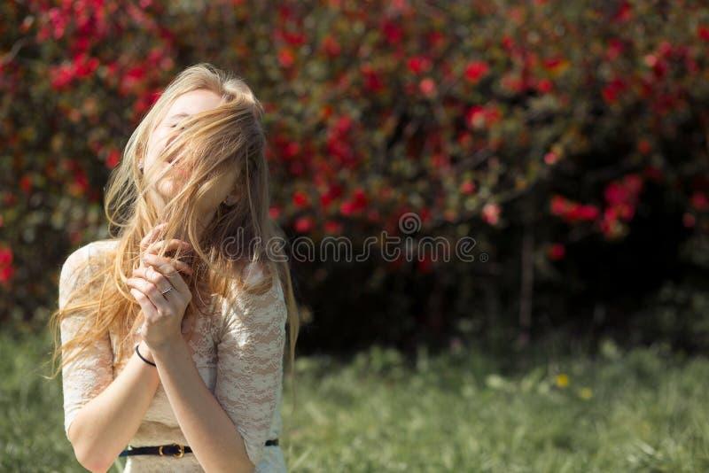 Giovane donna bionda che gode del giardino di fioritura dell'aroma nell'aria Lei occhi è chiusa da capelli da piacere fotografia stock libera da diritti