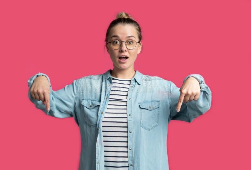 Giovane donna bionda che indica le dita giù che mostrano qualcosa, isolato sopra fondo rosa immagine stock libera da diritti