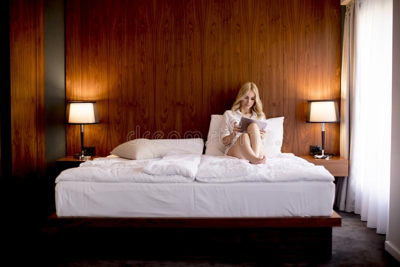 Giovane donna bionda che per mezzo della compressa digitale a letto fotografia stock libera da diritti