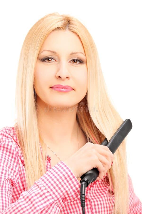 Giovane donna bionda che raddrizza i suoi capelli immagini stock