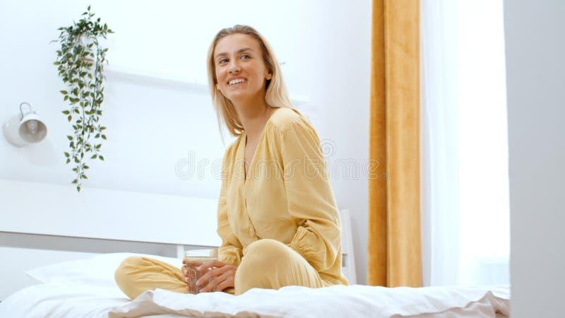 Giovane donna bionda che scrive sul telefono mentre sedendosi su un letto fotografia stock