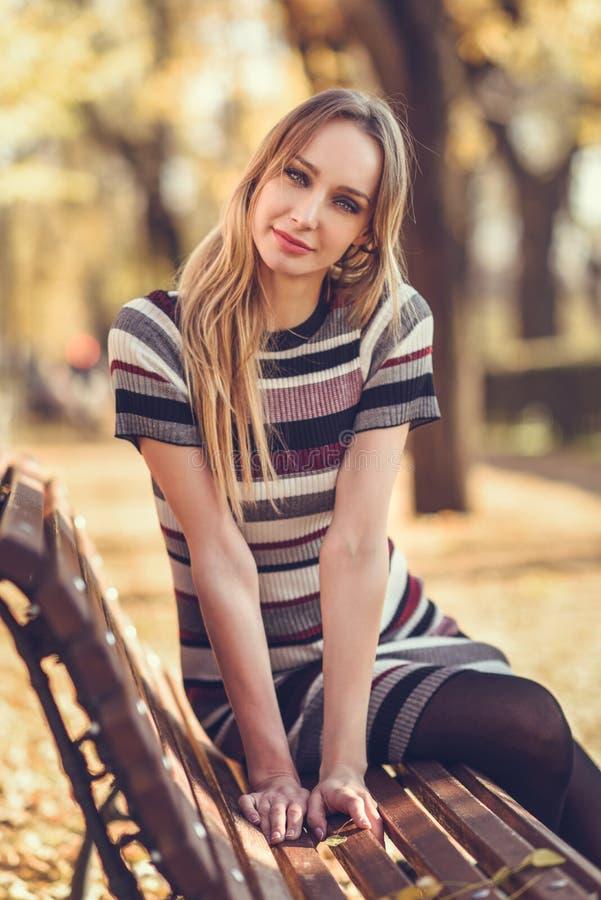 Giovane donna bionda che si siede su un banco di un parco immagini stock