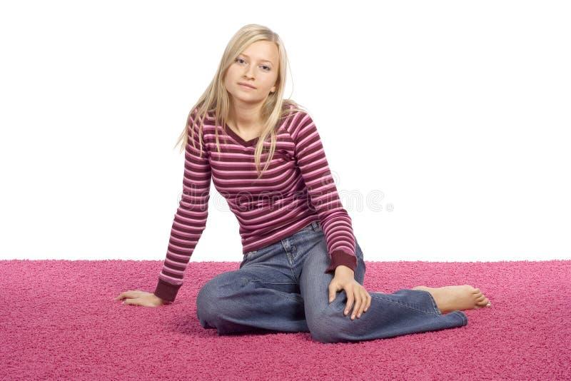 Giovane donna bionda che si siede sulla moquette dentellare fotografie stock libere da diritti