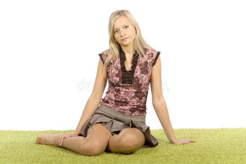 Giovane donna bionda che si siede sulla moquette verde immagini stock libere da diritti