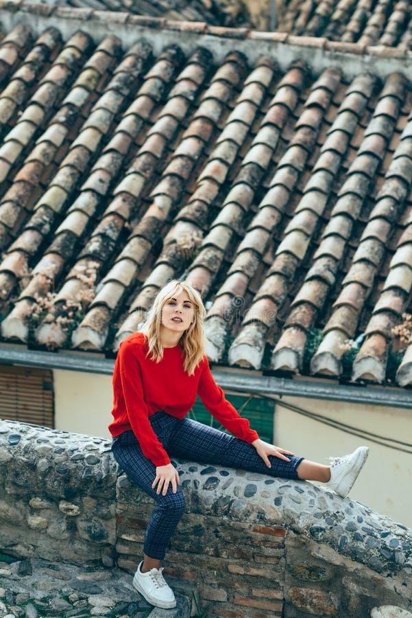 Giovane donna bionda che si siede vicino ai bei tetti di incantare le vecchie case fotografia stock libera da diritti