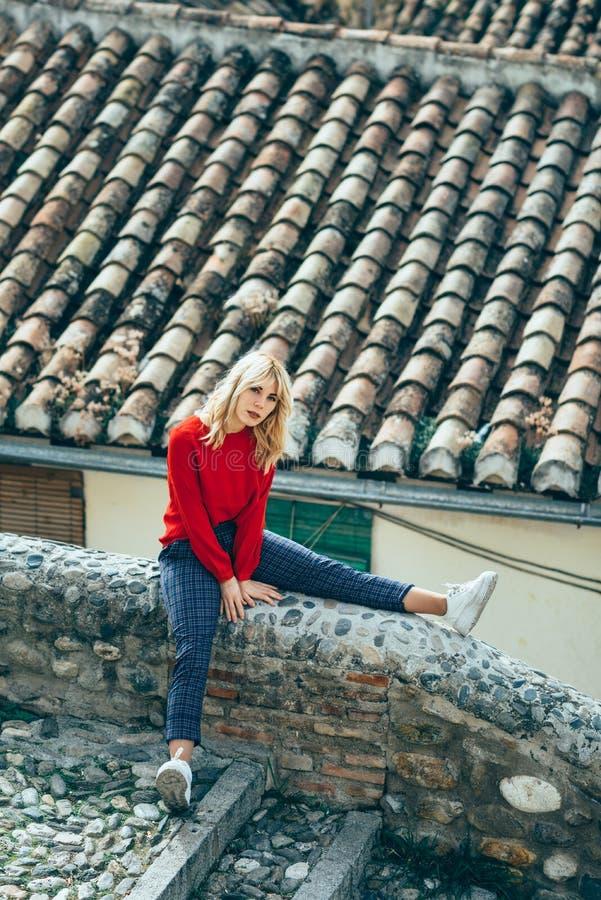 Giovane donna bionda che si siede vicino ai bei tetti di incantare vecchia h fotografie stock