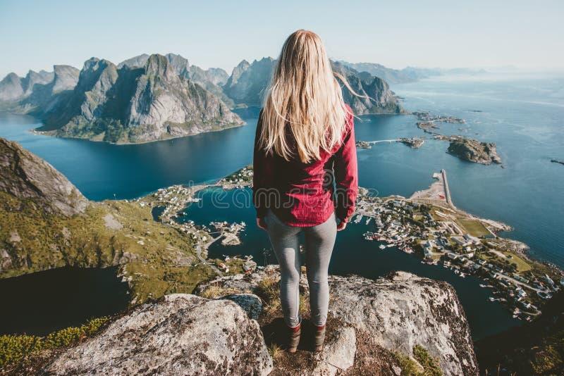 Giovane donna bionda che sta da solo sulla montagna della scogliera fotografia stock