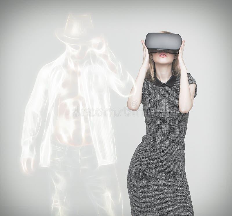 Giovane donna bionda con VR che mostra l'uomo sexy del ballerino immagini stock libere da diritti