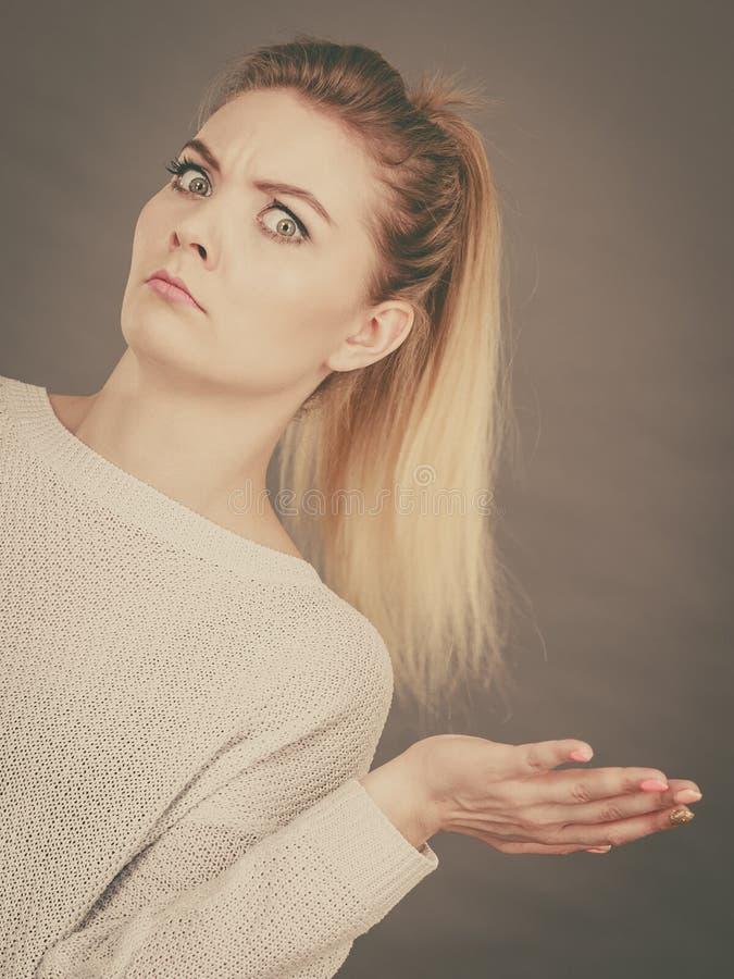 Giovane donna bionda confusa che gesturing con le mani fotografia stock libera da diritti