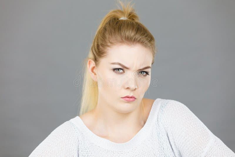 Giovane donna bionda confusa che sembra sospettosa fotografie stock