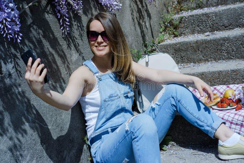 Giovane donna bionda dei pantaloni a vita bassa in occhiali da sole, facenti selfie, facendo uso della s immagine stock libera da diritti