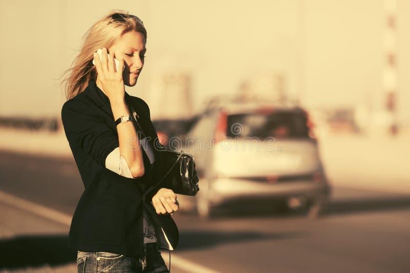 Giovane donna bionda di affari di modo che rivolge al telefono cellulare all'aperto fotografia stock