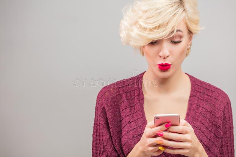 Giovane donna bionda di Stylysh che chiama mandare un sms ed usando al isola del telefono immagini stock