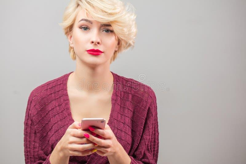 Giovane donna bionda di Stylysh che chiama mandare un sms ed usando al isola del telefono immagine stock