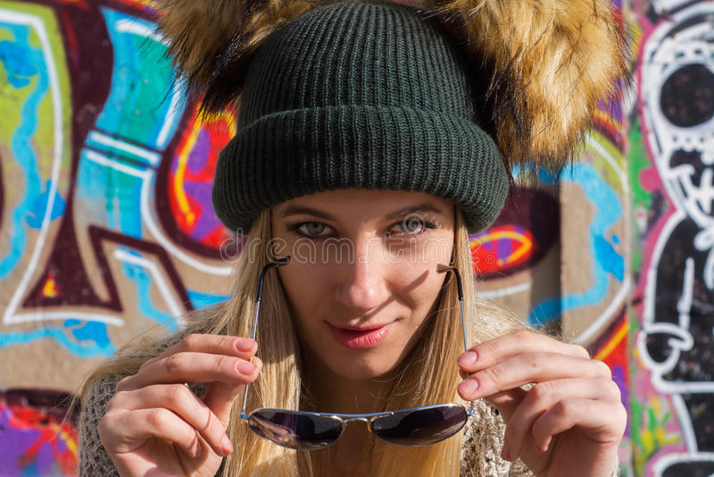 Giovane donna bionda divertente in cappello ed occhiali da sole che esaminano macchina fotografica fotografie stock