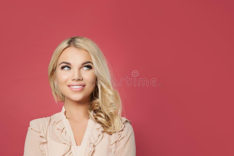 Giovane donna bionda felice che cerca ritratto Fronte sveglio della ragazza su fondo rosa immagine stock