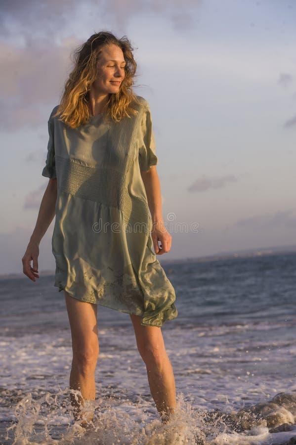 Giovane donna bionda felice e bella divertendosi alla spiaggia in vestito elegante da modo che gioca con la sensibilità del mare  immagine stock libera da diritti