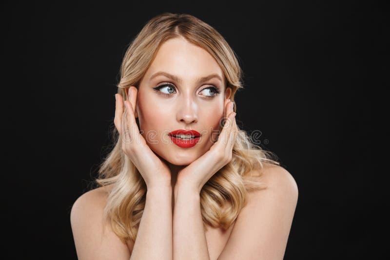Giovane donna bionda graziosa con la posa rossa delle labbra di trucco luminoso isolata sopra il fondo nero della parete immagine stock