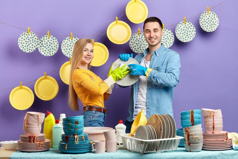Giovane donna bionda in maglione giallo ed in uomo castana che lavano i piatti fotografia stock libera da diritti