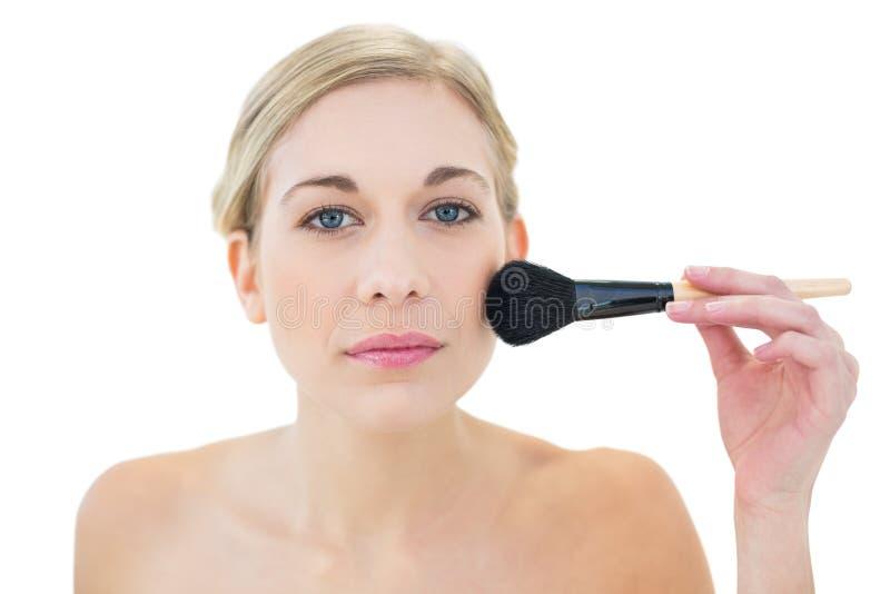 Giovane donna bionda naturale che applica polvere sulla sua guancia fotografia stock