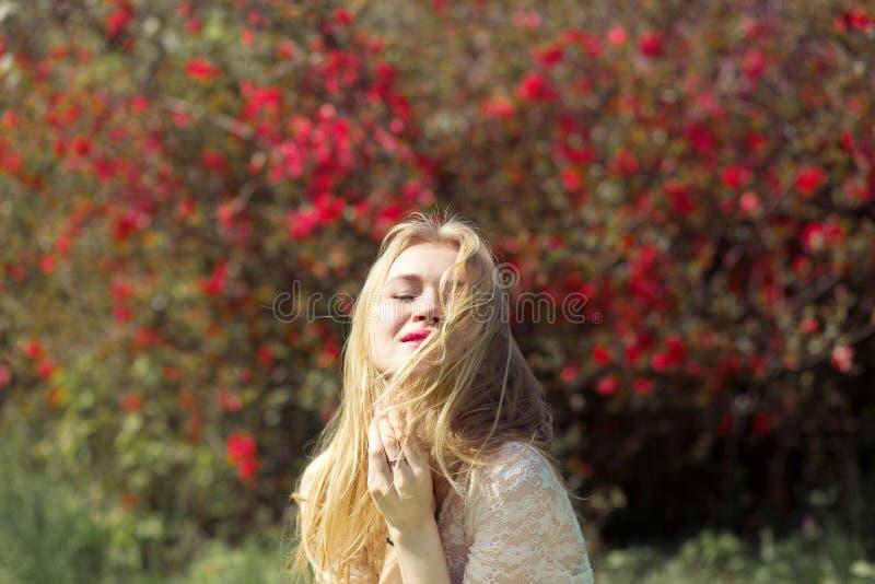 Giovane donna bionda nel giardino di primavera La ragazza con naturale perfetto compone la tenuta dei suoi capelli e godere della fotografia stock libera da diritti