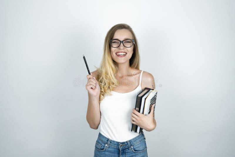 Giovane donna bionda nella penna di tenuta di vetro in una mano e libri nel suo altro fondo bianco sorridente della mano fotografia stock