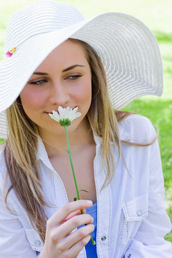 Giovane donna bionda pacifica che odora un fiore bianco immagine stock libera da diritti