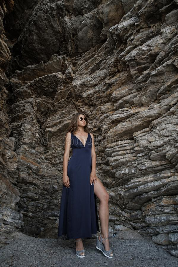 Giovane donna bionda riccia in vestito lungo contro roccia dal mare immagini stock