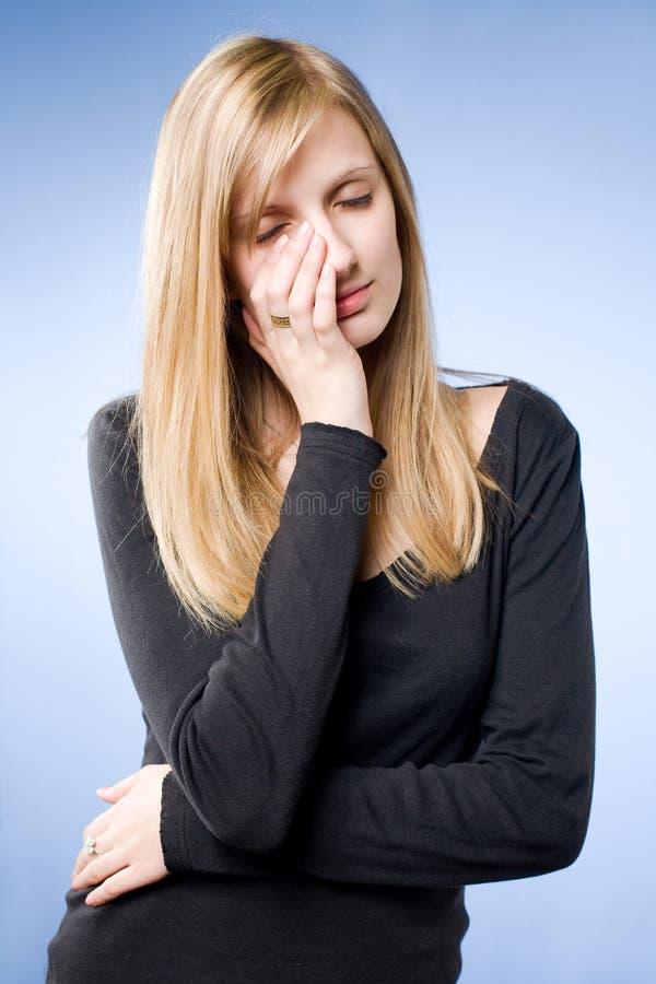 Giovane donna bionda sembrante triste. immagini stock