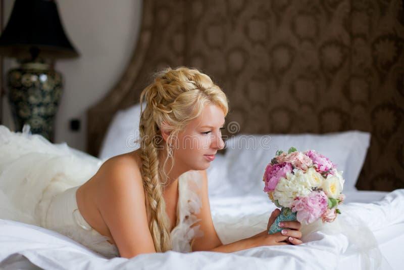 Giovane donna bionda sexy in camera da letto che mette su letto fotografia stock libera da diritti