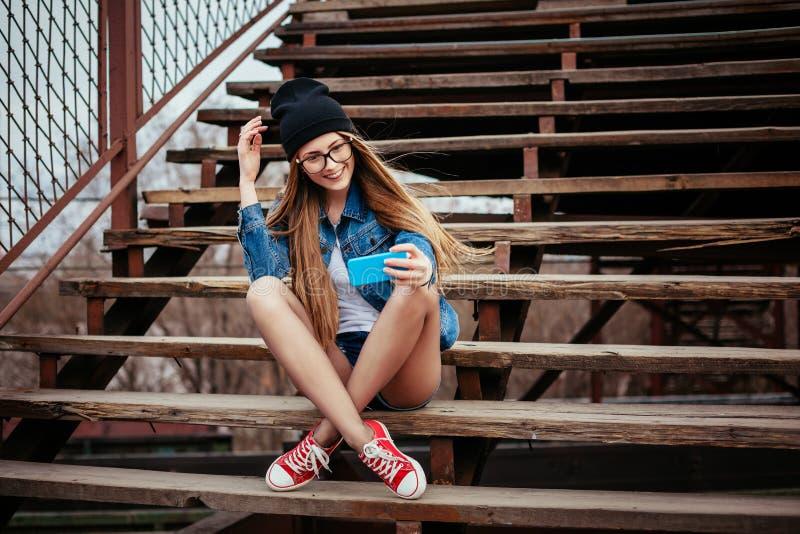 Giovane donna bionda sexy dei pantaloni a vita bassa che posa per il selfie e ridere Jeans d'uso rivestimento, pantaloni a vita b immagini stock libere da diritti