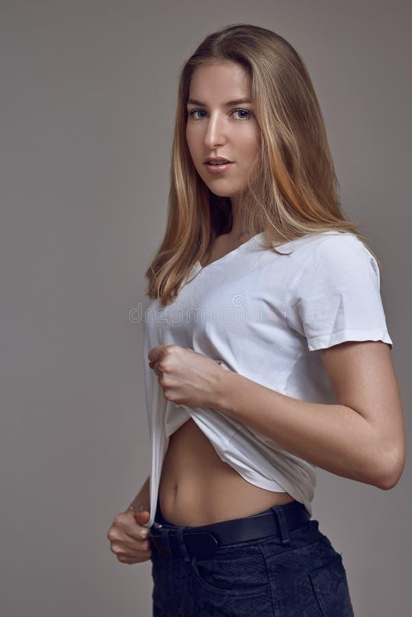 Giovane donna bionda sexy snella attraente in jeans ed in una maglietta bianca fotografia stock