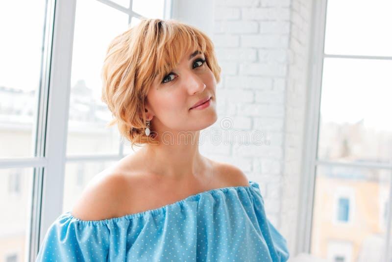 Giovane donna bionda sorridente affascinante dei capelli di scarsit? in vestito blu da estate vicino alla finestra nella stanza b fotografie stock