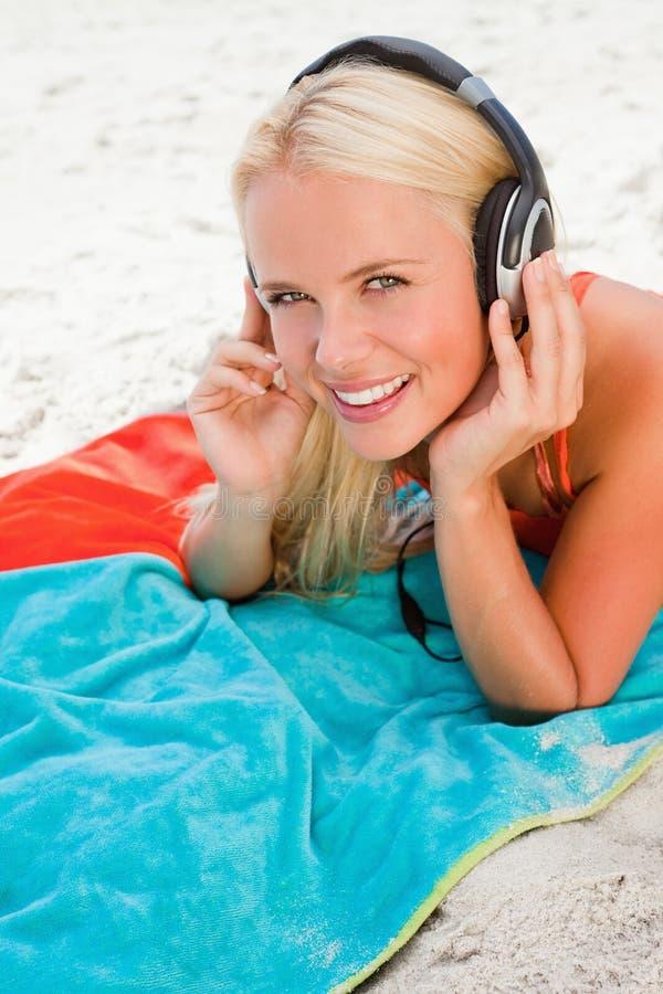 Giovane donna bionda sorridente che esamina la macchina fotografica mentre ascoltando la musica immagini stock