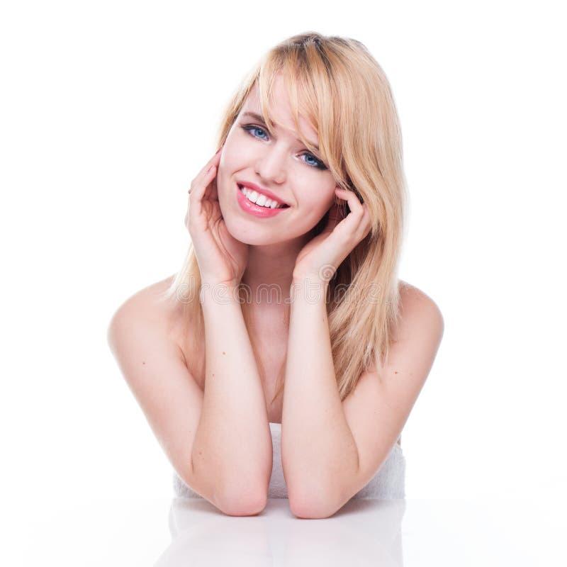 Giovane donna bionda sorridente con la testa in mani immagini stock libere da diritti