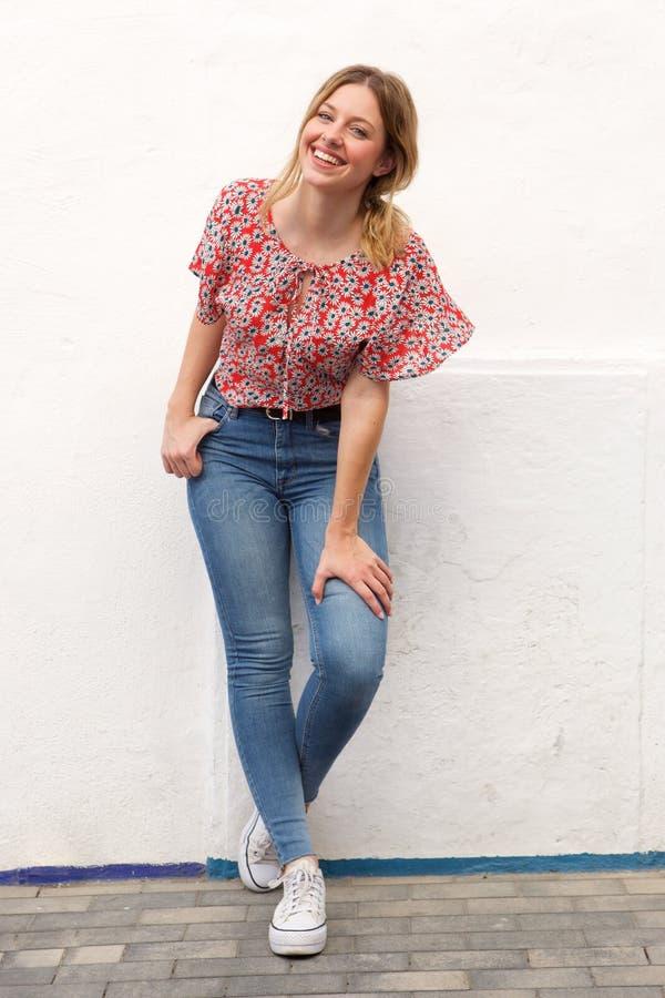 Giovane donna bionda sorridente integrale in jeans contro la parete bianca immagine stock