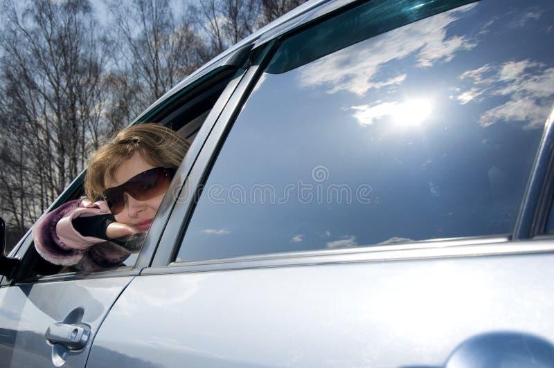 Giovane donna bionda in un'automobile blu in occhiali da sole fotografie stock