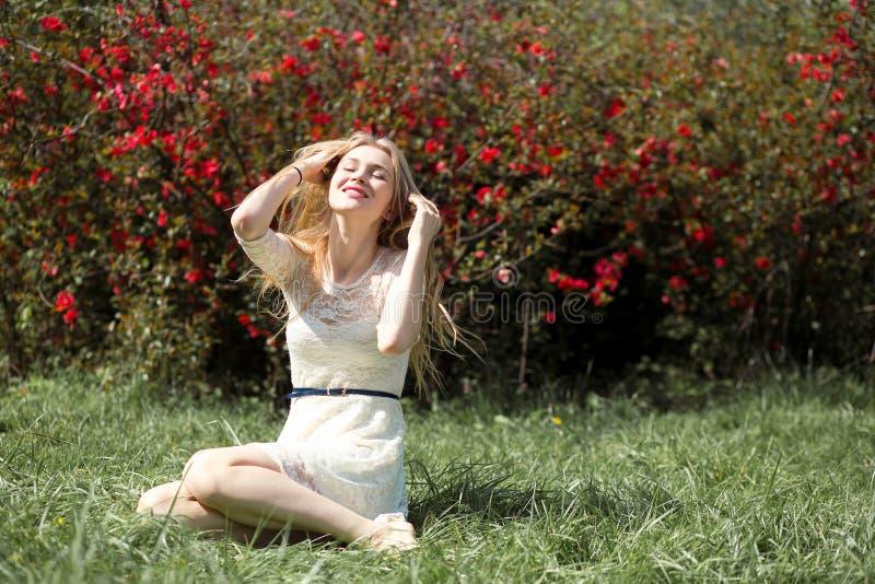 Giovane donna bionda in vestito bianco di pizzo che gode del giardino di fioritura dell'aroma nell'aria Ragazza che si siede sull immagini stock libere da diritti